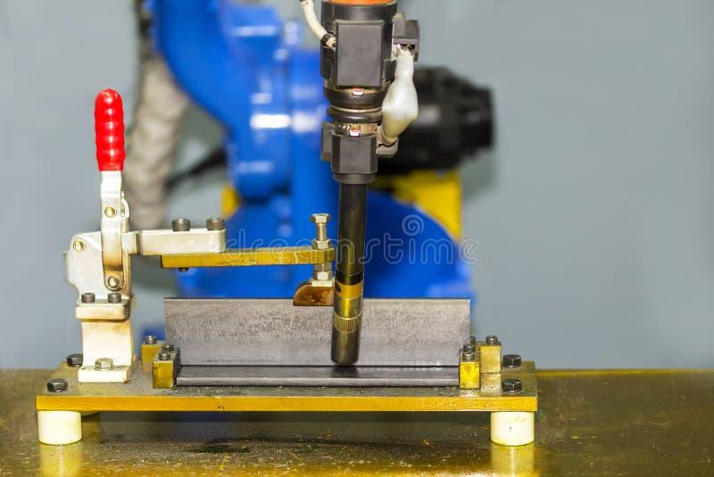 Giunto di T alto vicino di messa a punto dei pezzi in lavorazione sulla tavola per il processo elettrico della saldatura di MIG d fotografia stock libera da diritti