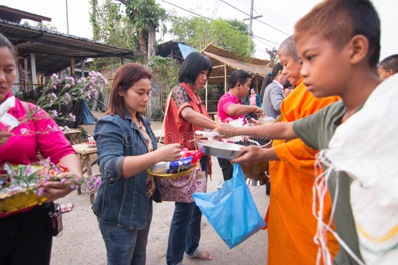 Give food offerings to a Buddhist monk in Morning. KANCHANABURI, THAILAND - MAR 25, 2015: Unknown People, give food offerings to a Buddhist monk in Morning royalty free stock photography