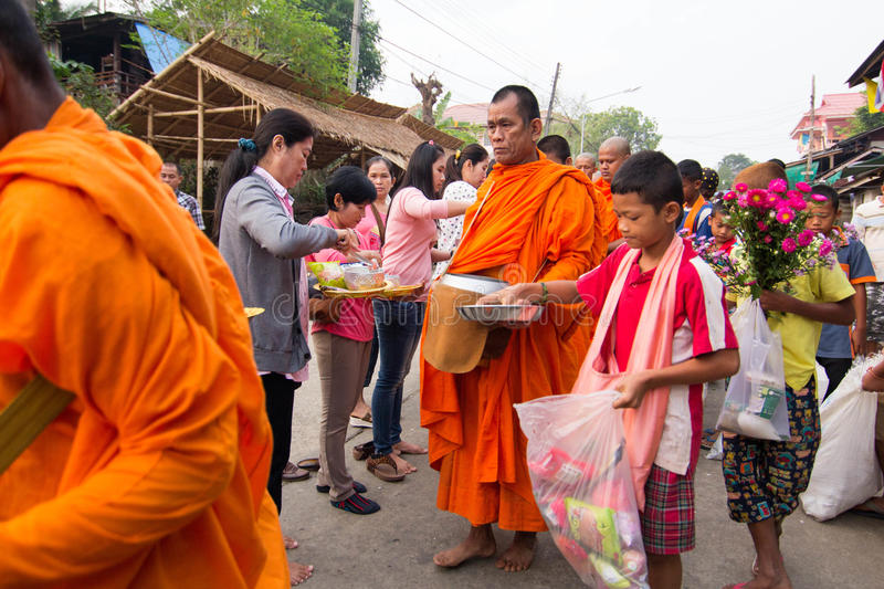 Give food offerings to a Buddhist monk in Morning. KANCHANABURI, THAILAND - MAR 25, 2015: Unknown People, give food offerings to a Buddhist monk in Morning royalty free stock images