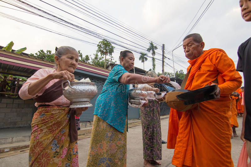 Give food offerings to a Buddhist monk in Morning. KANCHANABURI, THAILAND - MAR 25, 2015: Unknown People, give food offerings to a Buddhist monk in Morning stock photos