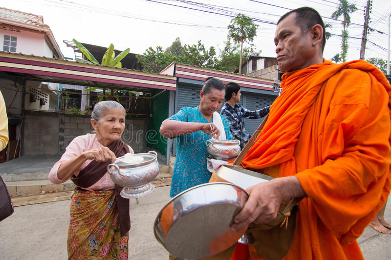 Give food offerings to a Buddhist monk in Morning. KANCHANABURI, THAILAND - MAR 25, 2015: Unknown People, give food offerings to a Buddhist monk in Morning stock images