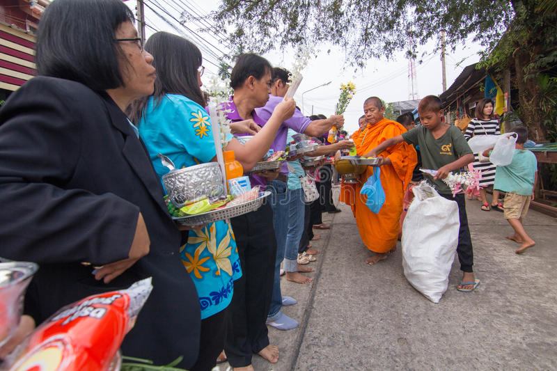 Give food offerings to a Buddhist monk in Morning. KANCHANABURI, THAILAND - MAR 25, 2015: Unknown People, give food offerings to a Buddhist monk in Morning royalty free stock photos