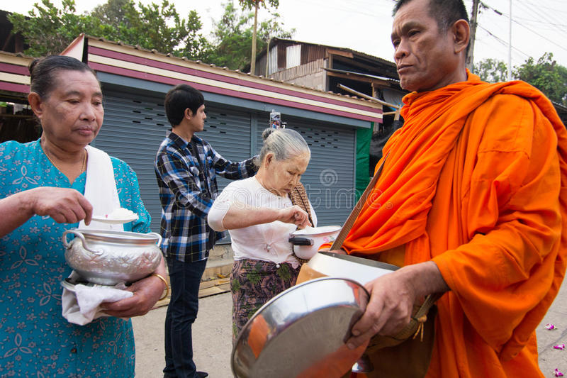 Give food offerings to a Buddhist monk in Morning. KANCHANABURI, THAILAND - MAR 25, 2015: Unknown People, give food offerings to a Buddhist monk in Morning stock photo
