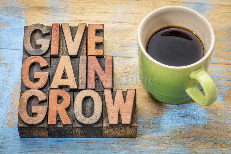 Give, gain and grow word abstract. Personal development or motivational concept - text in vintage letterpress wood type printing blocks with a cup of coffee stock photo