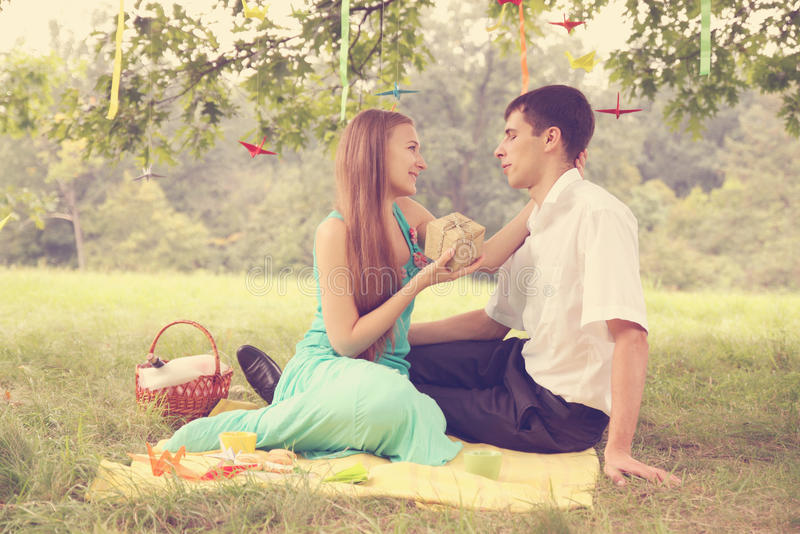 Give a gift. Woman gives a gift to his beloved man royalty free stock photos