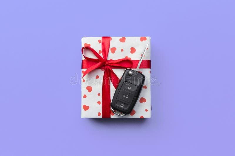 Give gift car key concept top view. Present box with red ribbon bow, heart and car key on purple colored background royalty free stock images