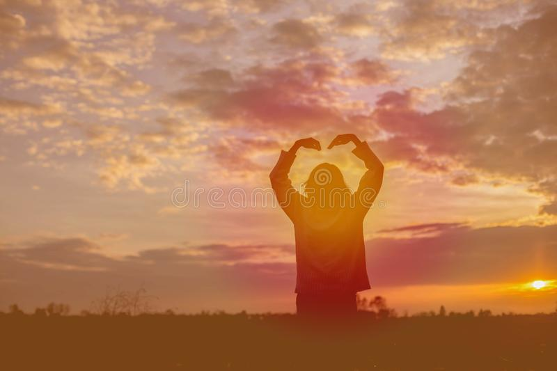 Give the gift on the Day of LoveRomantic girl walking in a field in sunset light. Winter, autumn life stock image