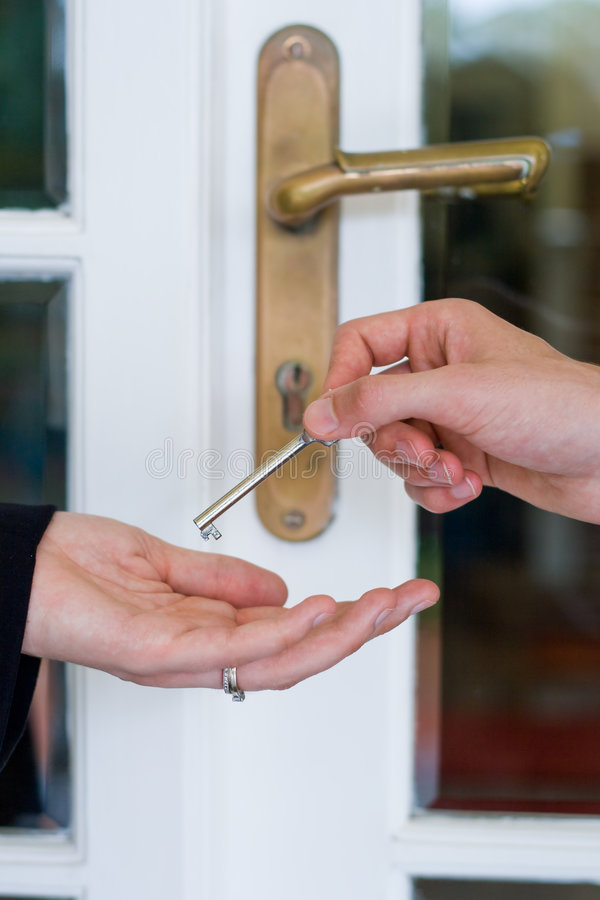 Give house key. Two hands give the house key in front of a glass door royalty free stock photography