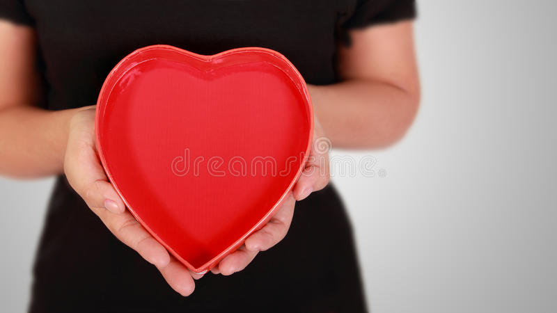 Give Love. Conceptual image of love/charity: close up of hands holding a red heart-shaped box royalty free stock photo