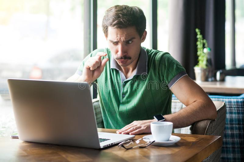 Give me a few more. Young businessman in green t-shirt sitting and looking at laptop display on video call and asking to give him stock photos