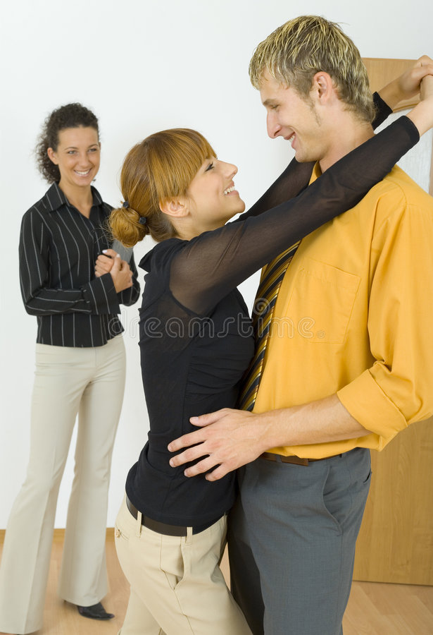 Give me a kiss. Three people standing in flat. One couple is hugging, other woman is standing alone and looking at them. Everyone smiling. Side view royalty free stock photo