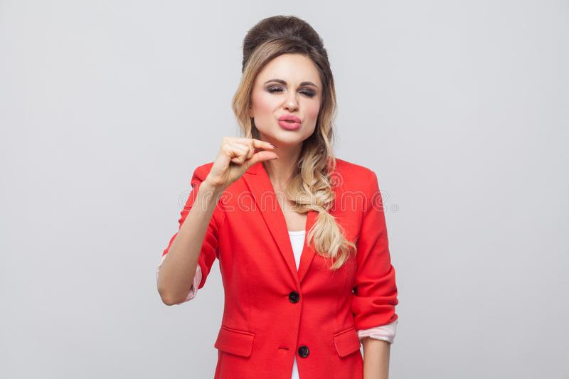 Give me a little bit more please. Beautiful business lady with hairstyle and makeup in red fancy blazer, standing and asking for a. Small thing more. indoor stock images