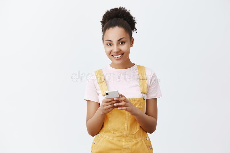 Give me your number. Portrait of charming flirty and feminine dark-skinned young woman in yellow overalls, holding stock photo