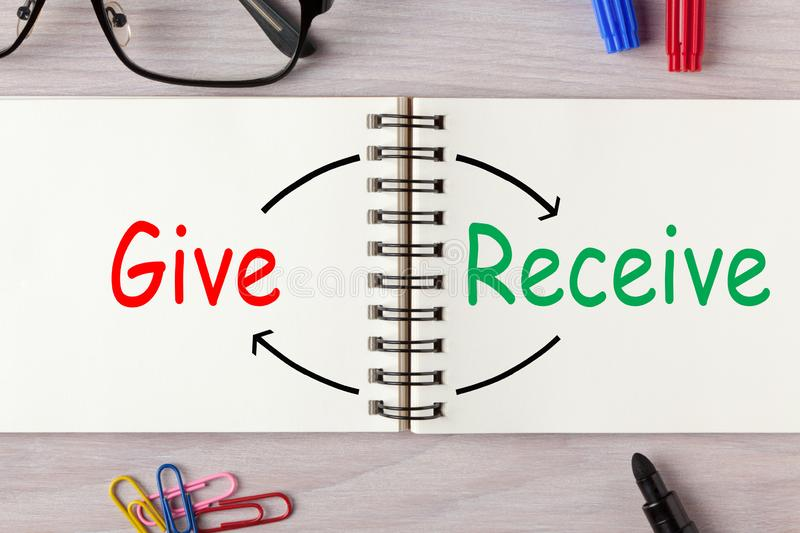Give Receive Donate. Give and Receive written on open spiral notebook and various stationery. Concept words royalty free stock photo