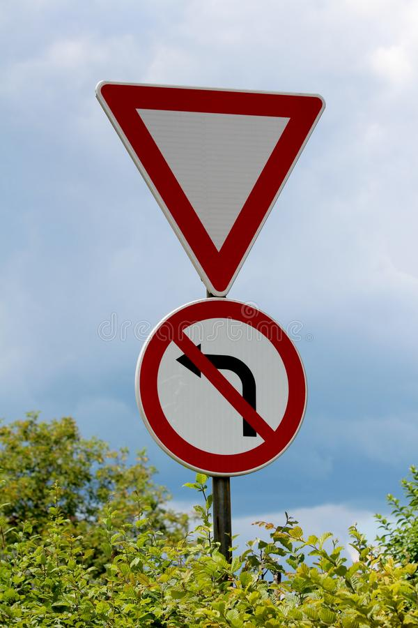 Give way and no left turn red and white signs mounted on strong metal pole surrounded with dense leaves on cloudy stormy blue sky stock photo