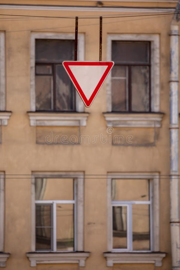 Give way Yield is a red and white triangle. Clear blue sky and the facade of the house behind the road sign. Give way traffic sign, yield, red and white royalty free stock photos