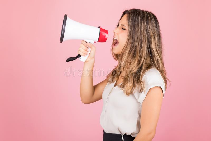 Give Your Cause A Voice. Confident bossy woman shouting into megaphone against pink background stock image