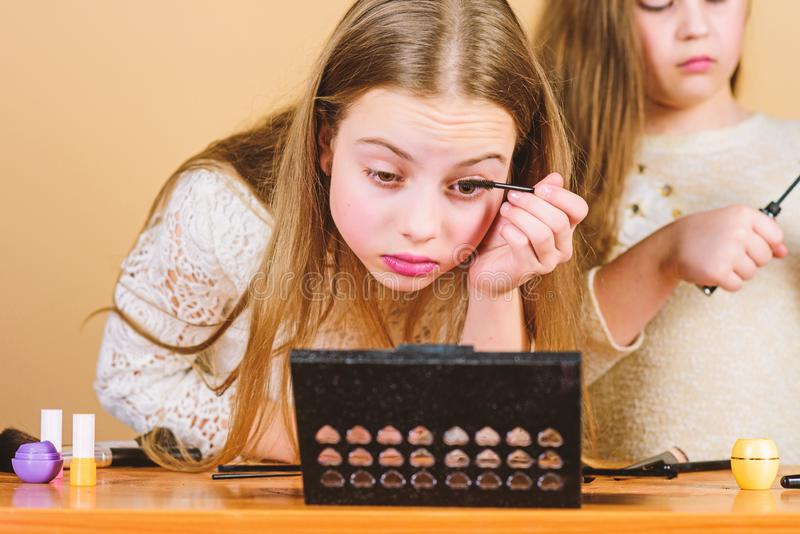 Give your lashes some extra flutter. Adorable kids doing eye lashes makeup. Little girls applying mascara on lashes stock photography