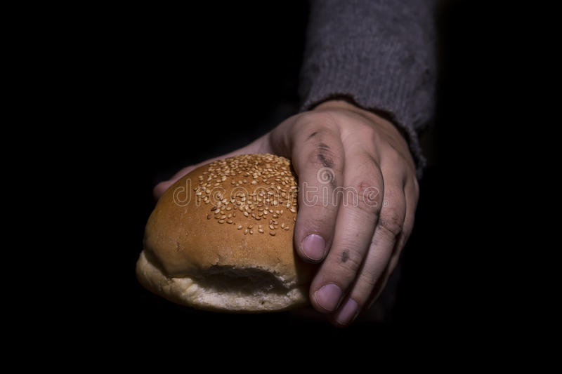 Giving bread. Poverty concept. Poverty concept. Dirty hands giving bread isolated on black background royalty free stock photography