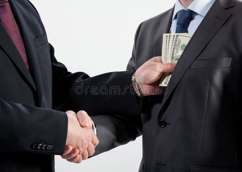 Giving a bribe into a pocket stock photos