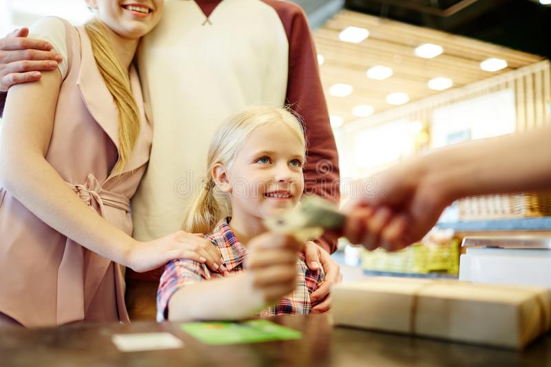 Giving cash to seller. Cute little girl giving cash to shop assistant while paying for goods stock image
