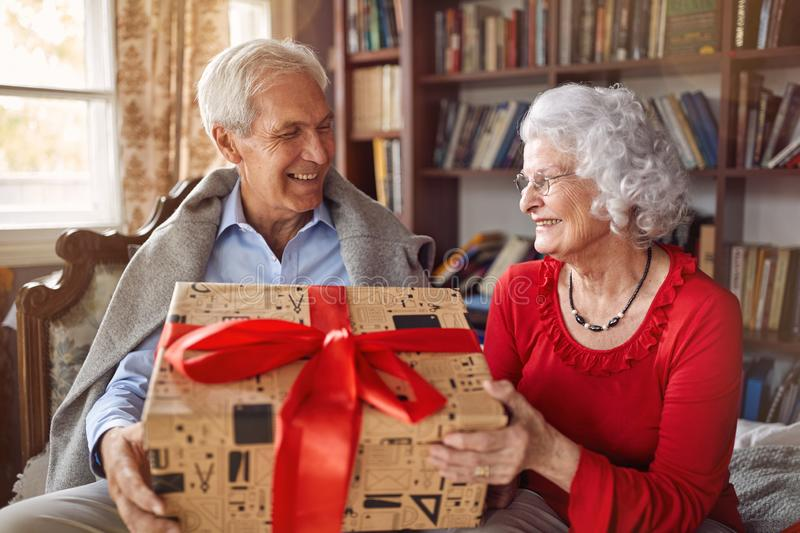 Giving Christmas gift on celebration time- senior man with presents spending Christmas together with woman. stock photography