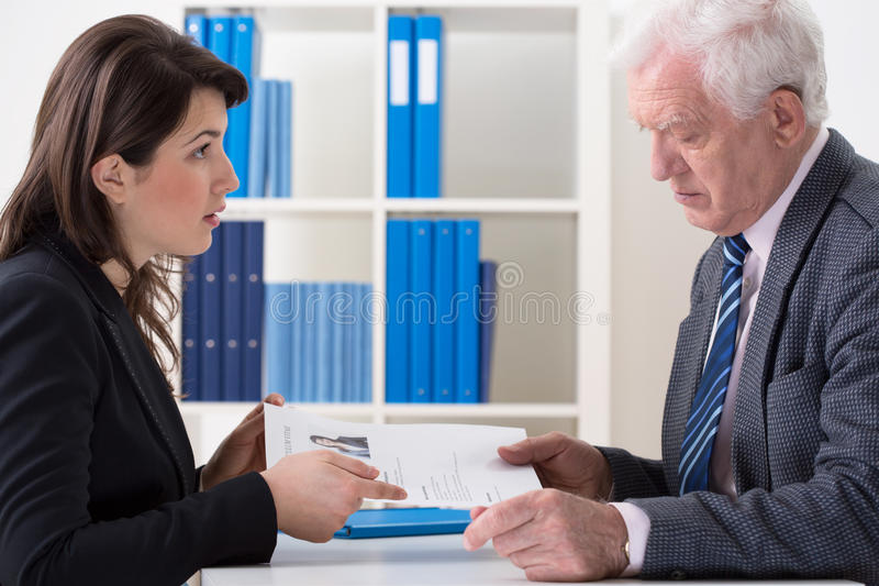 Giving the curriculum vitae. Young attractive women giving to the interviewer her curriculum vitae stock photo