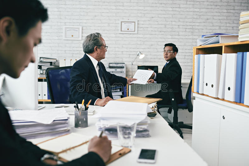 Giving document. Attorney giving important document to his coworker stock images