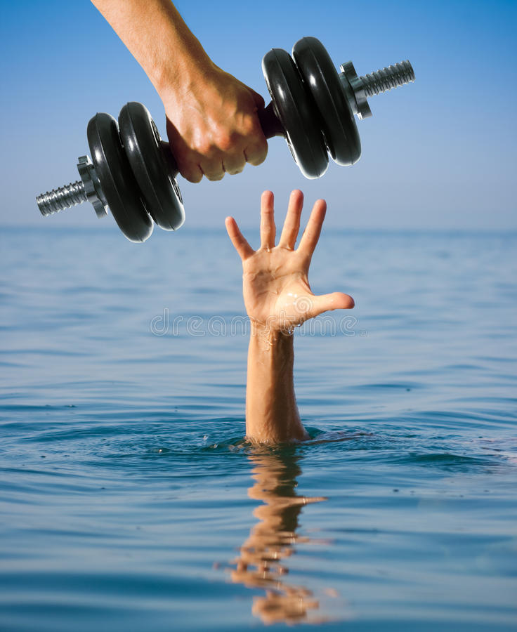 Giving dumbbell to sinking man instead of help. Making worse. stock image