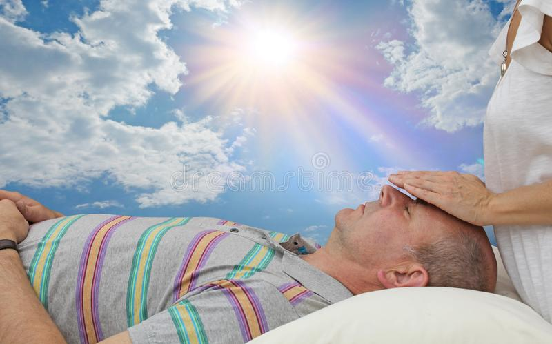 Giving an energy healing treatment out doors stock image