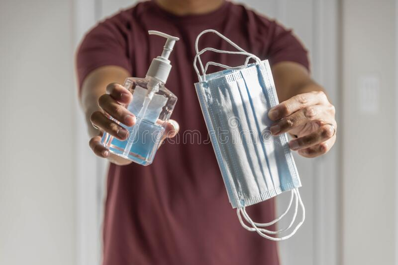 Giving face mask and hand sanitizer stock photos