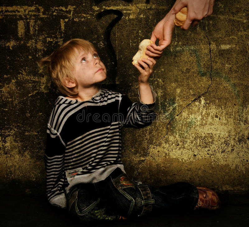 Giving food for homeless child. Giving food for homeless boy stock photography