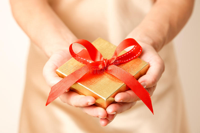 Giving a gift. Woman holding a gift box in a gesture of giving stock photos