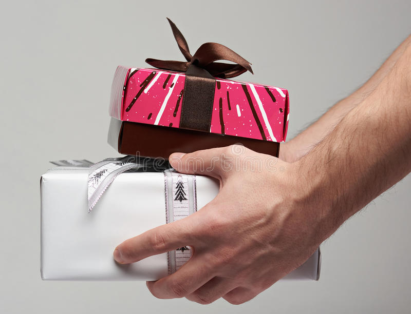 Giving gift boxes. Man giving gift boxes with ribbon close up view from side stock photo