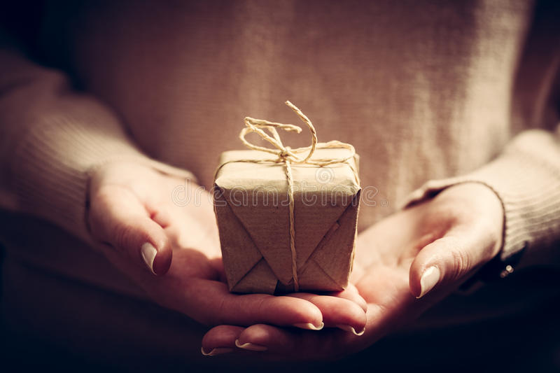 Giving a gift, handmade present wrapped in paper. Christmas time, vintage mood stock photography