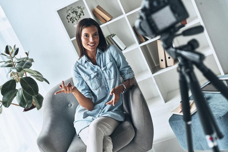 Giving good advice. Attractive young woman gesturing and smiling while making new video indoors royalty free stock images