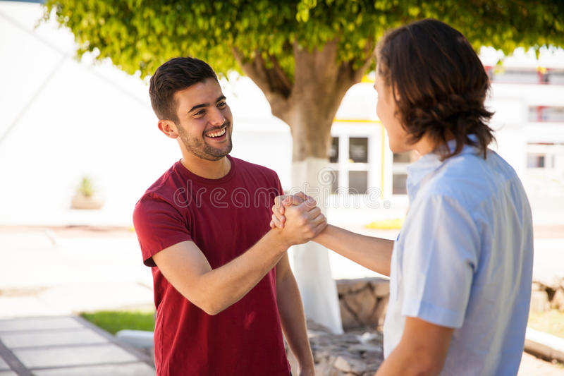 Giving a handshake at school. Pair of male friends greeting each other with a handshake at school stock photo