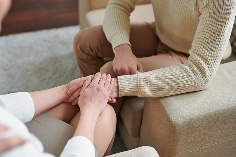 Giving help. Hands of counselor holding that of her patient while listening to his problems and helping to solve them royalty free stock photo