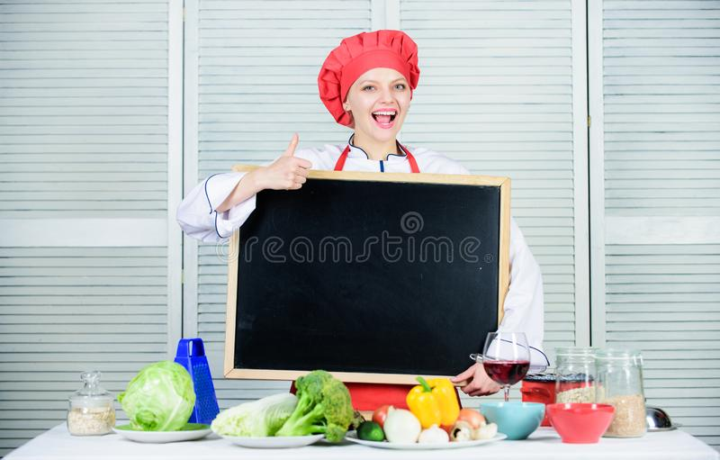 Giving her liking. Master cook gesturing thumbs up with empty blackboard. Chief cook teaching in cooking school. Master. Class in culinary school. Pretty woman royalty free stock images
