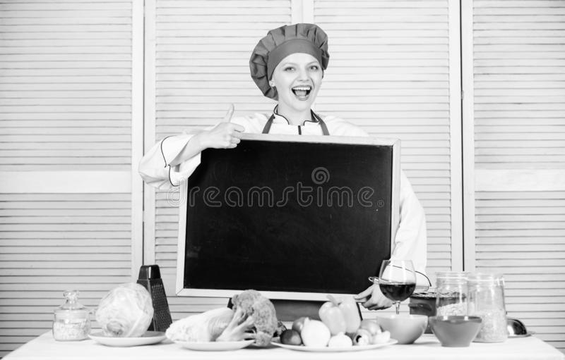 Giving her liking. Master cook gesturing thumbs up with empty blackboard. Chief cook teaching in cooking school. Master. Class in culinary school. Pretty woman royalty free stock photo