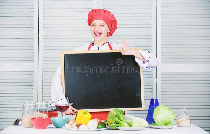 Giving her liking. Master cook gesturing thumbs up with empty blackboard. Chief cook teaching in cooking school. Master. Class in culinary school. Pretty woman stock photography