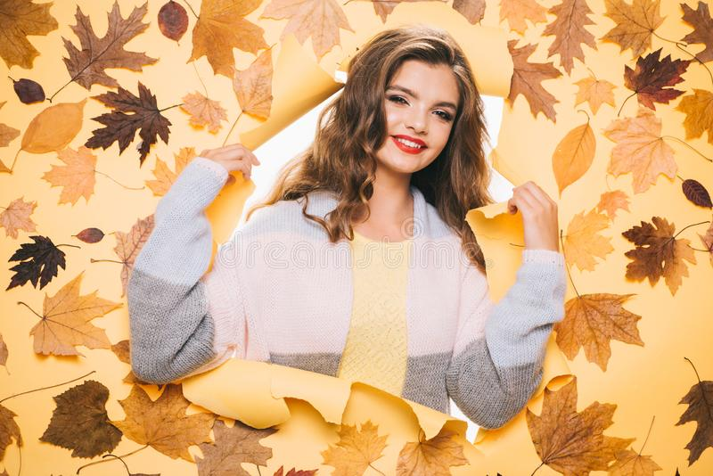 Giving her skintone a boost. Make-up trends for autumn. Fall look. Makeup girl peek through torn paper. Pretty girl look. Out of hole. Fashion model with royalty free stock photography