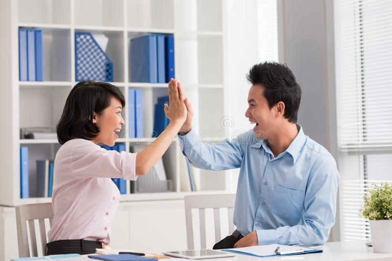 Giving high five. Young business people giving high five a symbol of success stock images