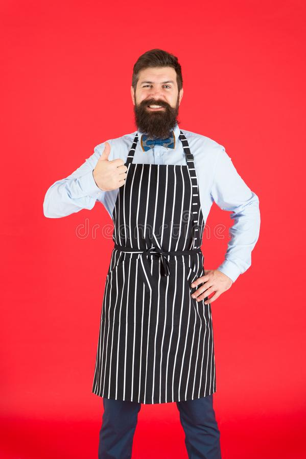 Giving his approval. Bearded man giving thumbs up approval hand gesture. Hipster gesturing approval sign. Cheerful cook. Or barista expressing his approval to stock photo