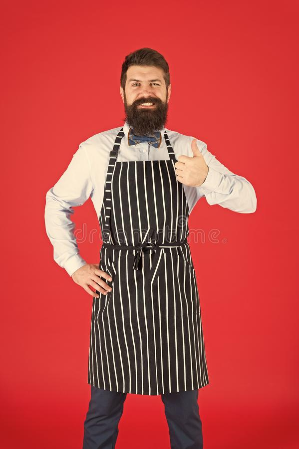 Giving his approval. Bearded man giving thumbs up approval hand gesture. Hipster gesturing approval sign. Cheerful cook stock image