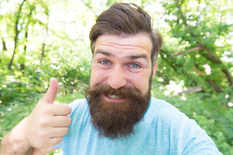 Giving his barber a thumbs up. Happy barber gesturing on natural landscape. Bearded man with shaped beard and mustache. Hair smiling before or after visiting royalty free stock photos