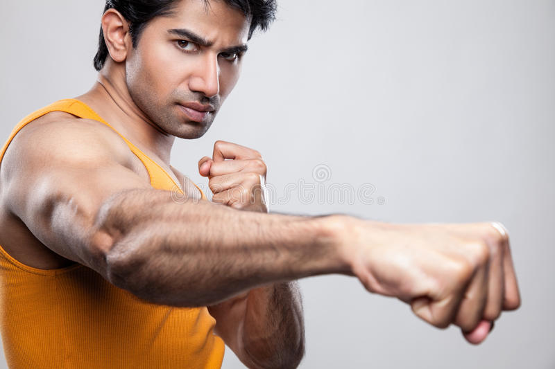 Giving a knockout punch. Handsome Indian man giving a knockout punch royalty free stock photography
