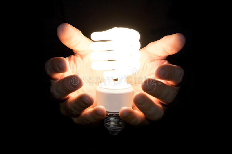Giving light. Man presenting glowing CFL (compact fluorescent) light bulb with his hands on black royalty free stock photo