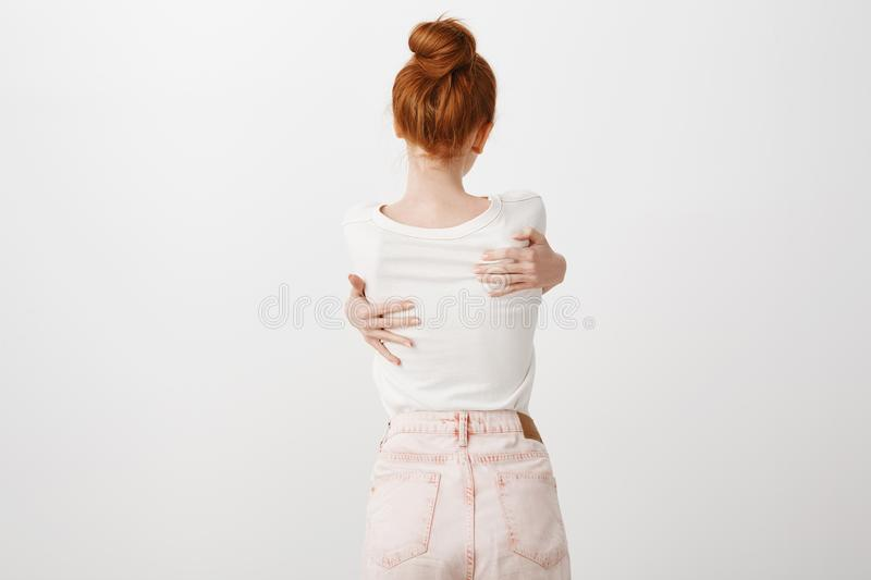 Giving myself warm hug to forget troubles. Portrait of thin young european redhead with bun hairstyle, hugging herself stock images