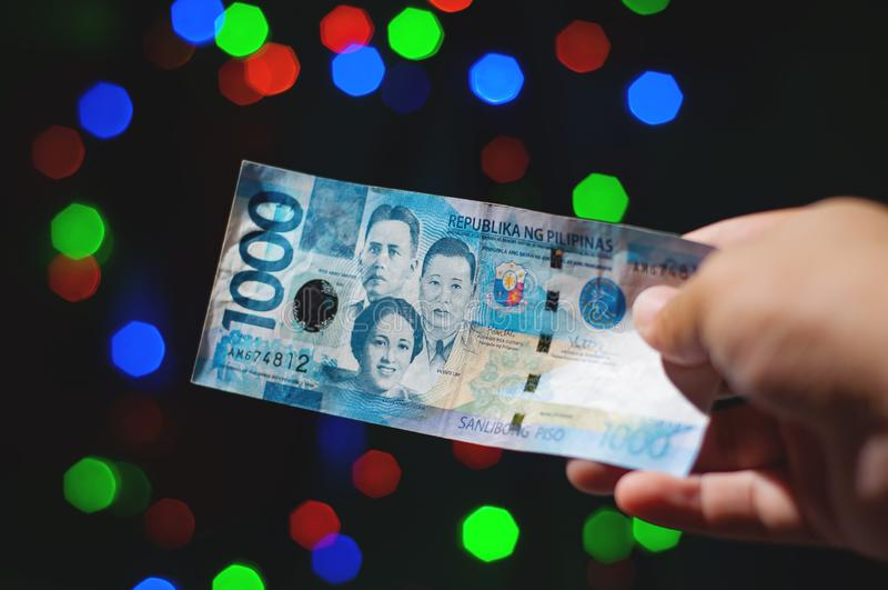 Giving a One Thousand Peso Cash on Christmas Day. A Filipino generous trait called Pamasko. Close up shot of a hand holding or handing out a Filipino One royalty free stock photo